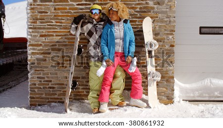 Close couple posing with snowboards against garage
