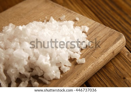 Close focus on sea salt presented on wooden board top view