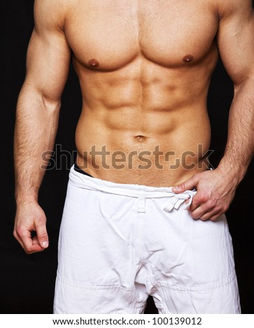 Close image of muscle man posing in studio - stock photo