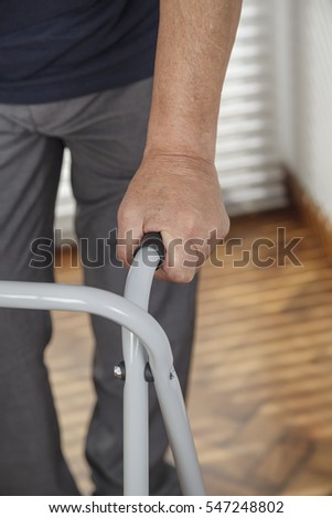 Close image of old retired man being helped by a nurse on his walker
