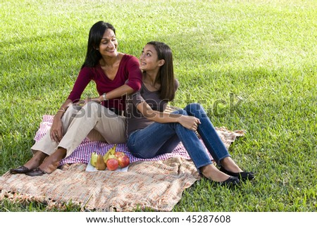 Close mother and daughter sitting on picnic blanket looking at each other - stock photo