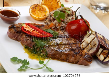 Close of of one piece cut of medium rare grilled steak with spicy herb sauce, garnished with grilled vegetables and organic brown rice. - stock photo