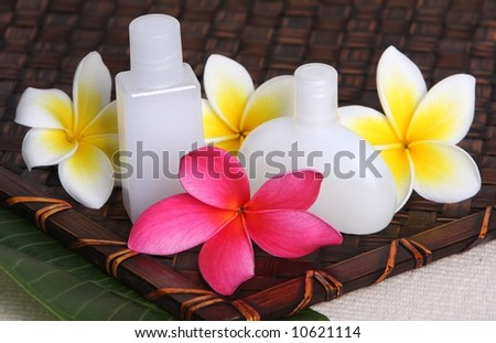 close of pink yellow and white frangiapani / plumeria flower with day spa beauty products on leaf and woven bamboo matt - stock photo