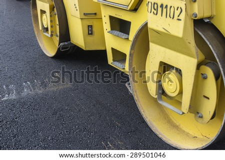 Close of road roller compacting asphalt. Compactor roller during street paving works. Selective focus and shallow dof. - stock photo