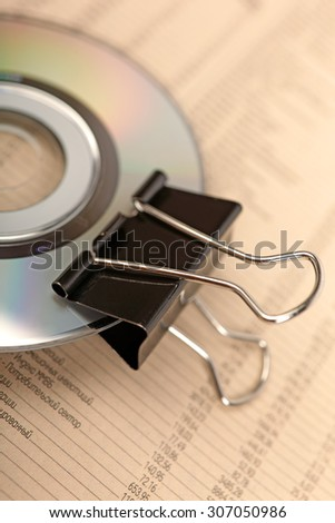 Close photo of paperclip attached to disk laying on financial newspaper. - stock photo