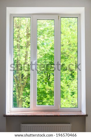 close plastic vinyl window on a background of green trees - stock photo