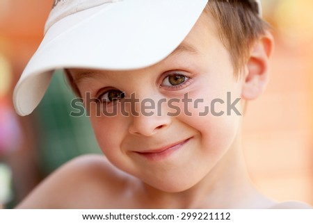 Close portrait of a boy with baseball cap, smiling - stock photo