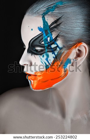 Close portrait of a girl in profile with paint on his face and streaks of paint. - stock photo