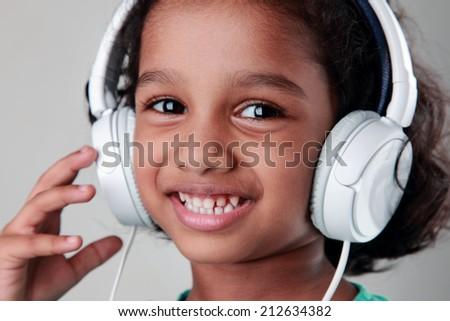 Close portrait of a girl listening music using headphone. - stock photo