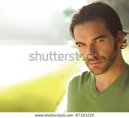 Close portrait of a good looking man outdoors with copy space - stock photo