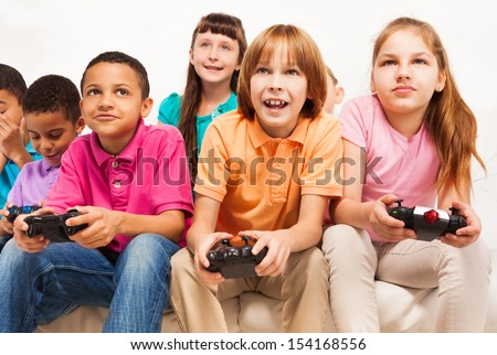Close portrait of a group of diversity looking kids, boys and girls playing videogame - stock photo