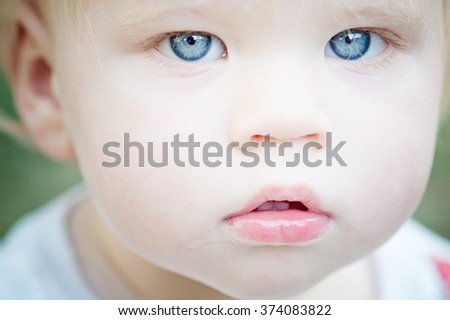 Close portrait of baby/toddler boy with bright blue eyes and pout on lips.