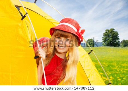 Close portrait of blond happy laughing little 10 years old girl sitting in camping tent in mountain yellow field - stock photo