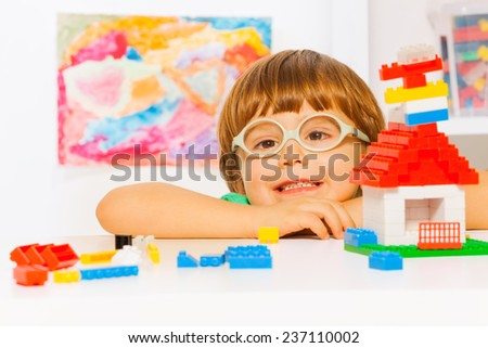 Close portrait of boy in glasses with blocks - stock photo