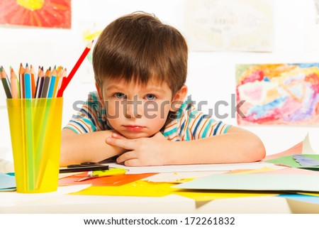 Close portrait of boy with pencils and color paper - stock photo