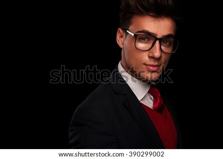 close portrait of handsome young man wearing glasses, looking at the camera while smiling in dark studio background - stock photo