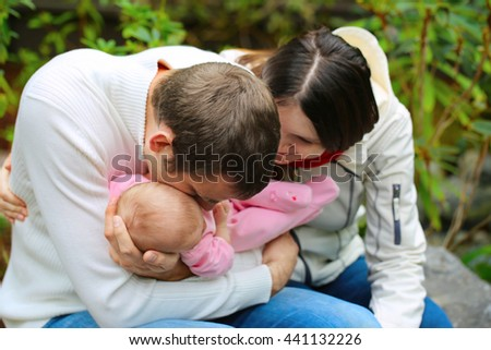 Close portrait of happy family together in the garden. Cute small baby in pink dress on father's hands. Parents kiss they baby girl - stock photo