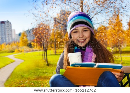 Close portrait of nice happy smiling 11 years old girl holding coffee mug and textbook wearing blue purple hat and scurf sitting on the bench in the park - stock photo