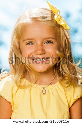 Close portrait of smiling blond little girl - stock photo