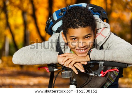 Close portrait of the nice black 10 years old boy laying on the bicycle stern - stock photo