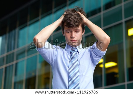 Close portrait of upset stressed handsome standing businessman, office building as background - stock photo