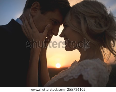 Close portrait silhouette in love wedding couple. Against the setting sun in the field. Lovers hug, girl tenderly holding her husband's face with both hands, smiling and looking into his eyes. - stock photo