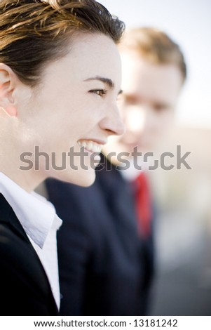 close profile view of attractive young businesswoman standing next to businessman who is looking at her - stock photo