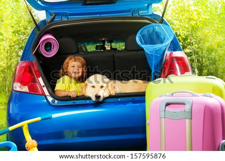 Close shoot of a car with retriever dog and 3 years old boy waiting in the trunk with bags for trip, trickle, ball, scoop-net - stock photo