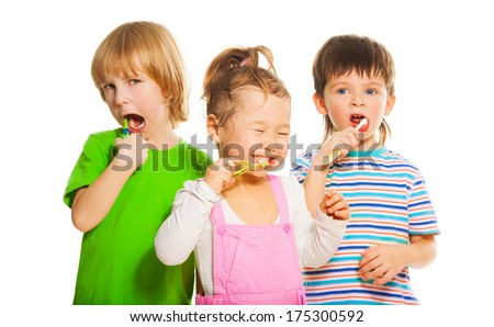 Close shoot of three happy little 3-4 years old kids standing with toothpaste - stock photo
