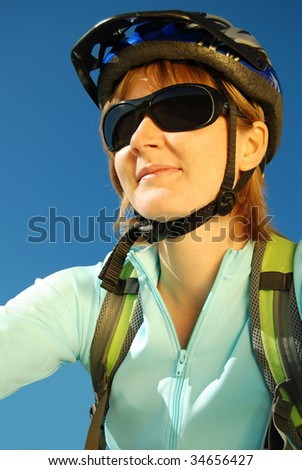 Close shot of a female cyclist with sunglasses and helmet - stock photo