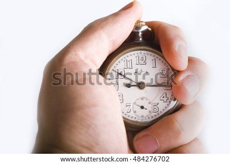 Close shot of a hand holding a watch isolated on a white background, caucasian/white.