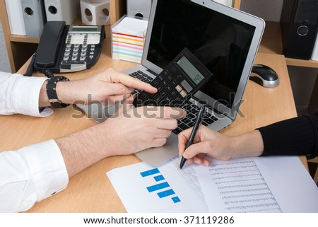 Close-shot of a hands, calculator, pen, and laptop, at business place