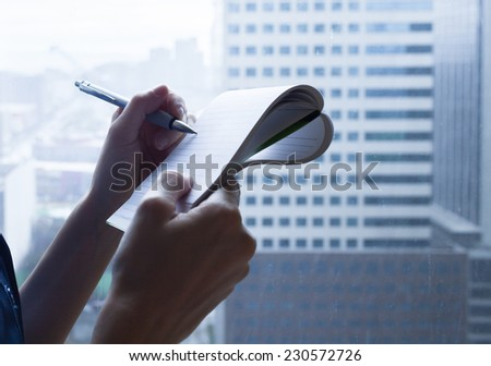 Close shot of a human hand writing something on a paper - stock photo