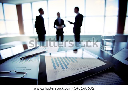 Close-shot of a tablet computer displaying financial data, three businessmen standing in the background - stock photo