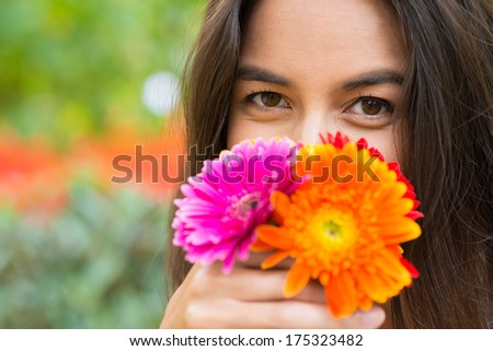 Close shot of a woman with gerberas flowers on the foreground  - stock photo