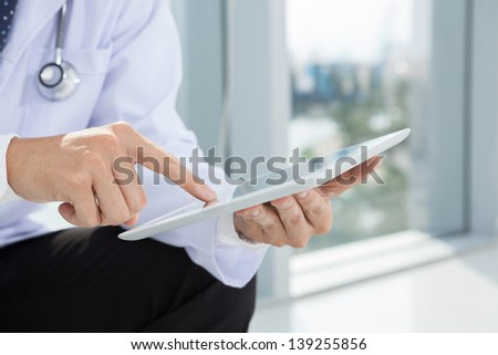 Close-shot of male hands holding a tablet in hands - stock photo