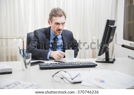 close shot of the hands attractive businessman working at business district office sitting at computer desk drinking coffee