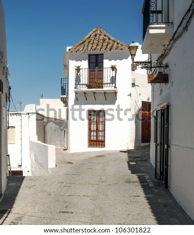 Close street decorated with white houses and bars in their windows. In the background are two paths. It is Situated in a village in Spain - stock photo