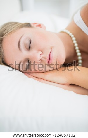 Close to a sleeping woman with pearls necklace in the white bedroom