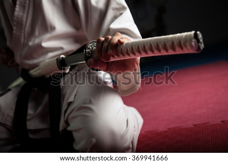 Close uo of young martial arts fighter with katana siting in seiza position