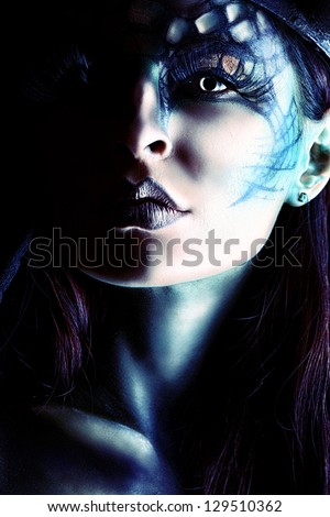 Close-uo portrait of a beautiful and scary devil woman. Art project. - stock photo
