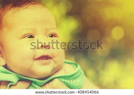 Close up a little infant cute smiling with bokeh nature background. Vintage or retro tone .Asian baby. - stock photo