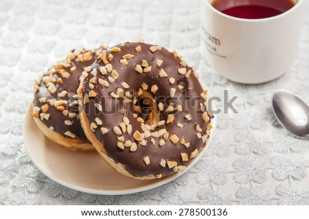 Close up a pair of chocolate donuts on a white plate decorated with mint  on kitchen table - stock photo