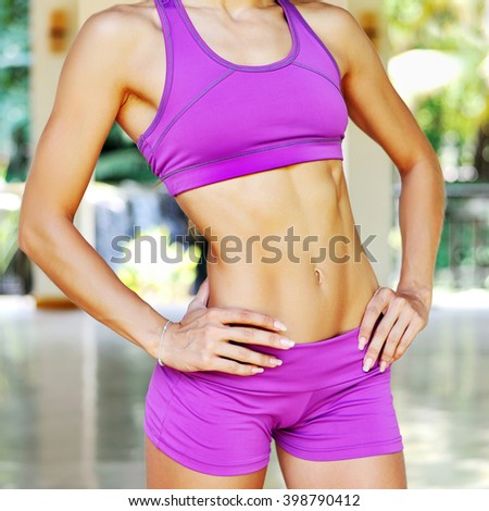 Close up abdominal muscles of young female athlete woman - stock photo
