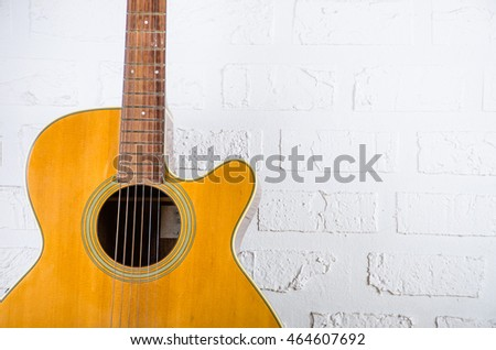close up Acoustic guitar on white wall and space for writing.