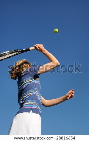 close up action shot of girl playing tennis - stock photo