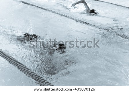 Close-up action shot of teen boy swimming front crawl stroke style in the water outdoor race pool. Focus on arm and water splash, some motion blurs. Swimming race, competition concept. Black and white