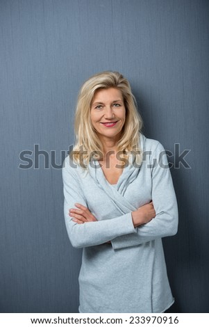 Close up Adult Blond Woman Crossing her Arms in Front her Body While Looking at Camera. Captured in Gray Wall Background. - stock photo
