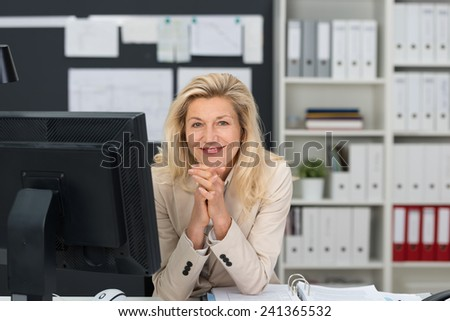 Close up Adult Businesswoman with Blond Hair Looking at Camera with Hands on the Chin. Captured at her Office with Computer on the Table. - stock photo