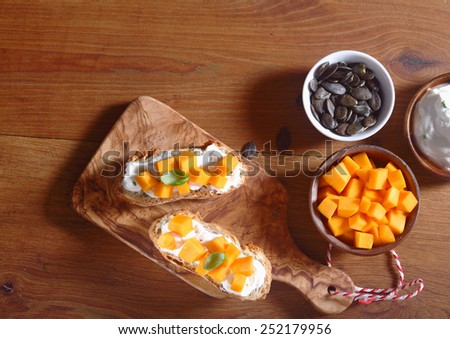 Close up Aerial Shot of Delicious Crusty Bread with Cream and Carrot Slice Fillings on Top of Wooden Board. Placed on Wooden Table Bowl of Carrot Slices and Pumpkin Seeds on the Side. - stock photo